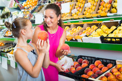 Mother with girl taking peaches on market Royalty Free Stock Image