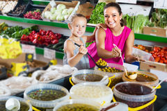 Mother with girl taking pickled olives to container Stock Photo
