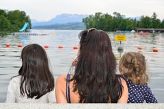 Mother and girls contemplating a lake. Mother and her girls contemplating a lake in a summer evening Royalty Free Stock Image