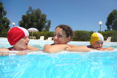 Mother and girls lie near skirting in pool Stock Photo