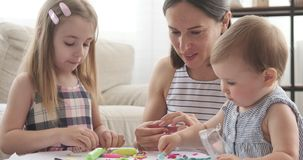 Mother and girls playing with plasticine. Mother and two little girls having fun playing with plasticine at home stock footage