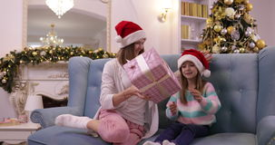 Mother Give Daughter Present Box Gift Happy Smiling Family On Couch Wear Santa Hat Decorated New Year Christmas Tree stock footage