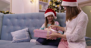 Mother Give Daughter Present Box Gift Happy Smiling Family On Couch Wear Santa Hat Decorated New Year Christmas Tree stock video