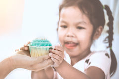 Mother give delicious blue cupcake to child girl. And holding together in vintage color tone Stock Photography