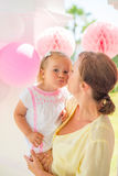 Mother Giver Sweet Kiss to Her Little Daughter. They Standing on Terrace during Birthday Party Stock Photography