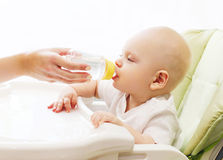 Mother gives baby water of plastic bottle at table home Stock Photos