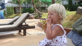 Mother Gives Banana to Little Girl near Pool. Mother gives banana to blonde little girl sitting on chaise longue near swimming pool against hotel buildings stock video