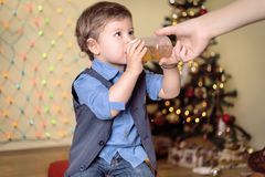 Mother gives a bottle to her son on a christmas eve. In front of a Christmas tree royalty free stock photos