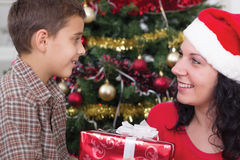 Mother gives boy a gift on Christmas night Royalty Free Stock Photo