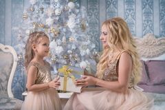 Mother gives a Christmas gift to her daughter Stock Photos