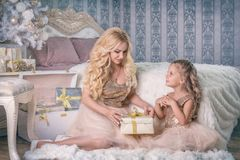 Mother gives a Christmas gift to her daughter Stock Photo