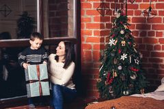 Mother gives gift to her son for Christmas. Mother gives gift to her son for Christmas stock photos
