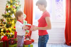 Mother gives a gift to her son for Christmas or son gives a gift to his Mom royalty free stock photos