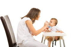 Mother gives her baby to eat yogurt Stock Photos