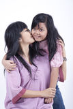 Mother gives a kiss to her daughter. Mother and Daughter happy family pose isolated on white Royalty Free Stock Photos