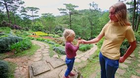 Mother Gives Little Girl Ice Cream Tube on Stone Path in Park stock video footage