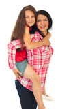 Mother gives piggy back ride to her daughter Stock Photo