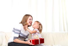 Mother gives present to dauthter and kissing. Mother gives present to her dauthter in red box and kissing at home Royalty Free Stock Photos