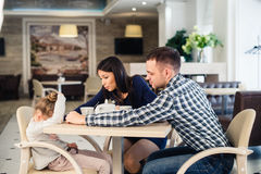 Mother gives solace to crying daughter at restaurant and angry father Stock Images
