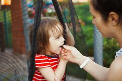 Mother gives to child bite of chocolate. restriction of the daughter from great large quantity sweets. The influence of desserts on the condition teeth Royalty Free Stock Photos