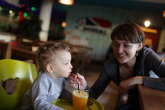 Mother gives to drink her son juice Royalty Free Stock Photos
