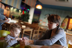 Mother gives to drink her toddler juice Royalty Free Stock Photo