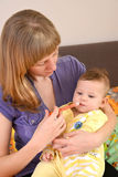 Mother gives to the sick baby medicine by means of the batcher Royalty Free Stock Images