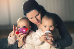 Mother gives twin babies bottles Royalty Free Stock Image
