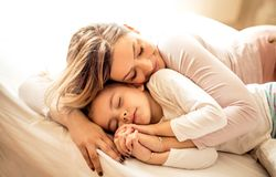 Mother gives us the warmest love. Mother and daughter playing on bed royalty free stock photos