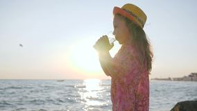 Mother gives water her daughter outdoors, little girl drinks clean water near sea, cute child in backlight keeps cup. At hands, beautiful kid at hat drinking stock footage
