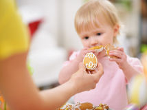 Mother giving baby cookie in shape of Easter egg. Stock Photos