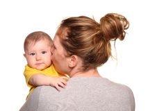 Mother giving baby girl a kiss on the cheek. Cutout Royalty Free Stock Image