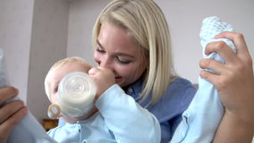 Mother Giving Baby Son Bottle Of Milk Stock Photography