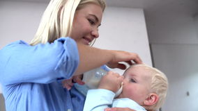 Mother Giving Baby Son Bottle Of Milk Royalty Free Stock Photo