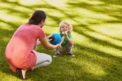 Mother giving ball to son. Mother giving a rugby ball to her little son Stock Image