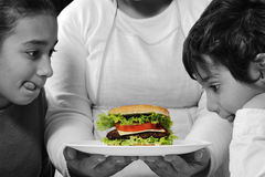 Mother giving a burger Royalty Free Stock Photography
