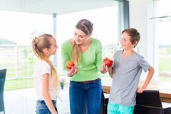 Mother giving children apple Royalty Free Stock Photo