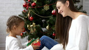 Mother giving Christmas gift to her child with Christmas tree on the background stock video footage