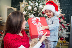 Mother giving Christmas present to her son. Stock Photos