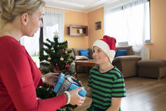 Mother giving Christmas present to her son. Royalty Free Stock Photography
