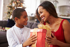 Mother Giving Christmas Presents To Son At Home Royalty Free Stock Images