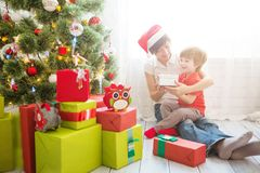 Mother giving Christmas presents to son at home stock photos