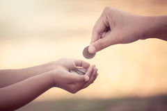 Mother giving coin to child as saving money concept. In vintage color tone royalty free stock photos