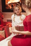 Mother giving daughter Christmas present royalty free stock image