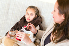 Mother giving daughter cough syrop. Caring mother gives her sick daughter cough syrop Stock Photos