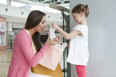 Mother giving daughter gift from paper shopping bag Royalty Free Stock Images