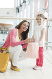 Mother giving daughter paper shopping bag Stock Image