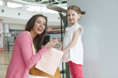 Mother giving daughter paper shopping bag Stock Photography
