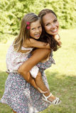 Mother giving daughter piggy back ride Stock Photos