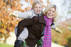 Mother giving daughter piggy back ride Stock Photography